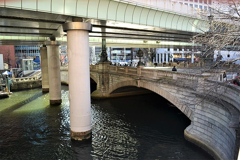 Первоначально мост Нихомбаси был деревянным, его построили в начале периода Эдо. Нынешний каменный мост с двумя арками (девятнадцатая реконструкция) был построен в 1911 году. Он пережил землетрясение и бомбардировки и продолжает функционировать как часть дорожной инфраструктуры города