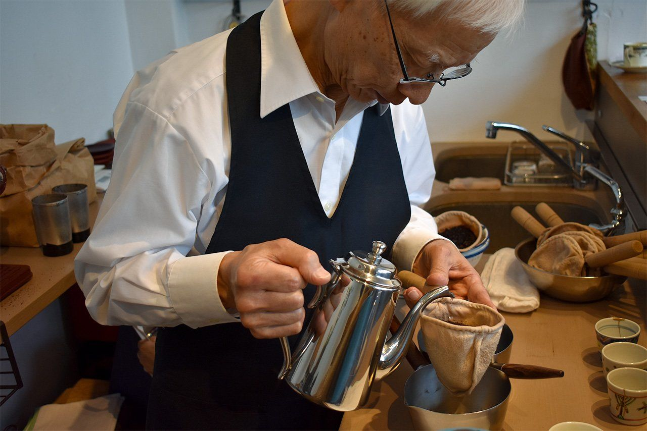 Дайбо готовит чашку кофе во время мероприятия в Омотэсандо