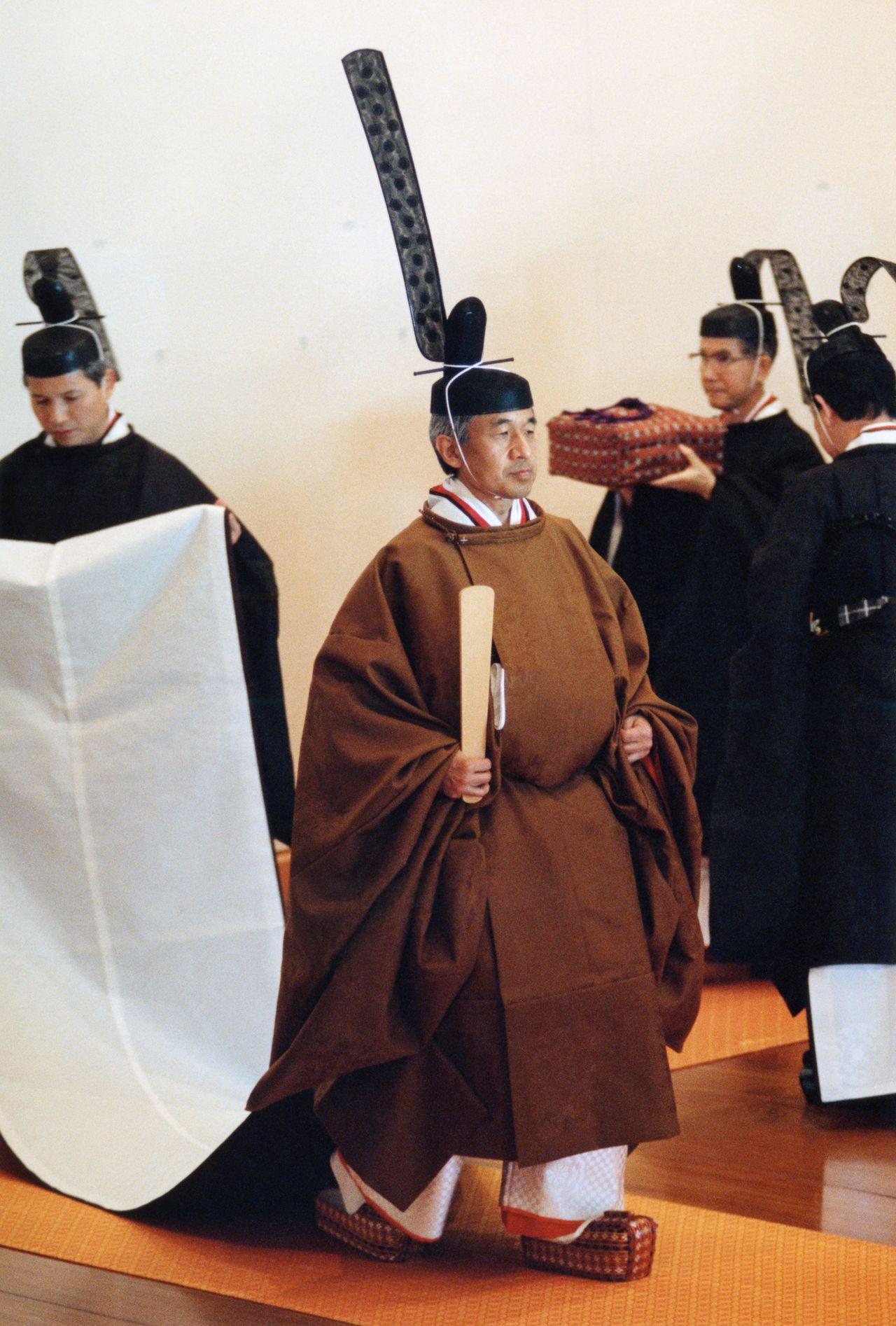 Император Акихито (нынешний почётный император) в церемониальной одежде кородзэн-но гохо во время церемонии Сокуирэй Сэйдэн-но ги. В узорах одежды использованы мотивы павловнии, бамбука, феникса, мифического животного кирин. В правой руке он держит церемониальную табличку сяку, он обут в сокай – обувь из дерева, украшенная парчой и напоминающая обувь синтоистских священников асагуцу. 12 ноября 1990 г., зал Мацу-но ма (Jiji Press)