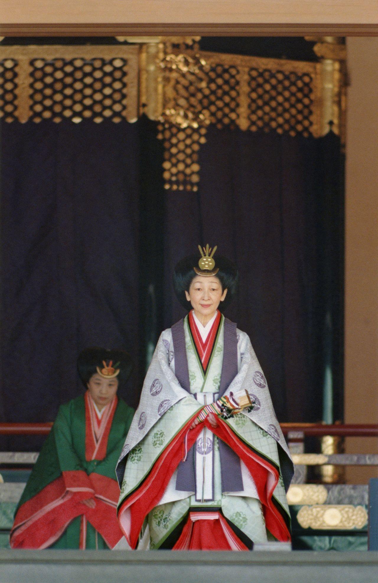 Императрица Митико (нынешняя почётная императрица) в церемониальной одежде дзюнихитоэ во время церемонии Сокуирэй Сэйдэн-но ги. Одежда дзюнихитоэ включает в себя кимоно типов ицуцугину, карагину, мо. Волосы уложены в причёску осубэракаси и украшены золотой заколкой сайси. 12 ноября 1990 г., зал Мацу-но ма (Jiji Press)