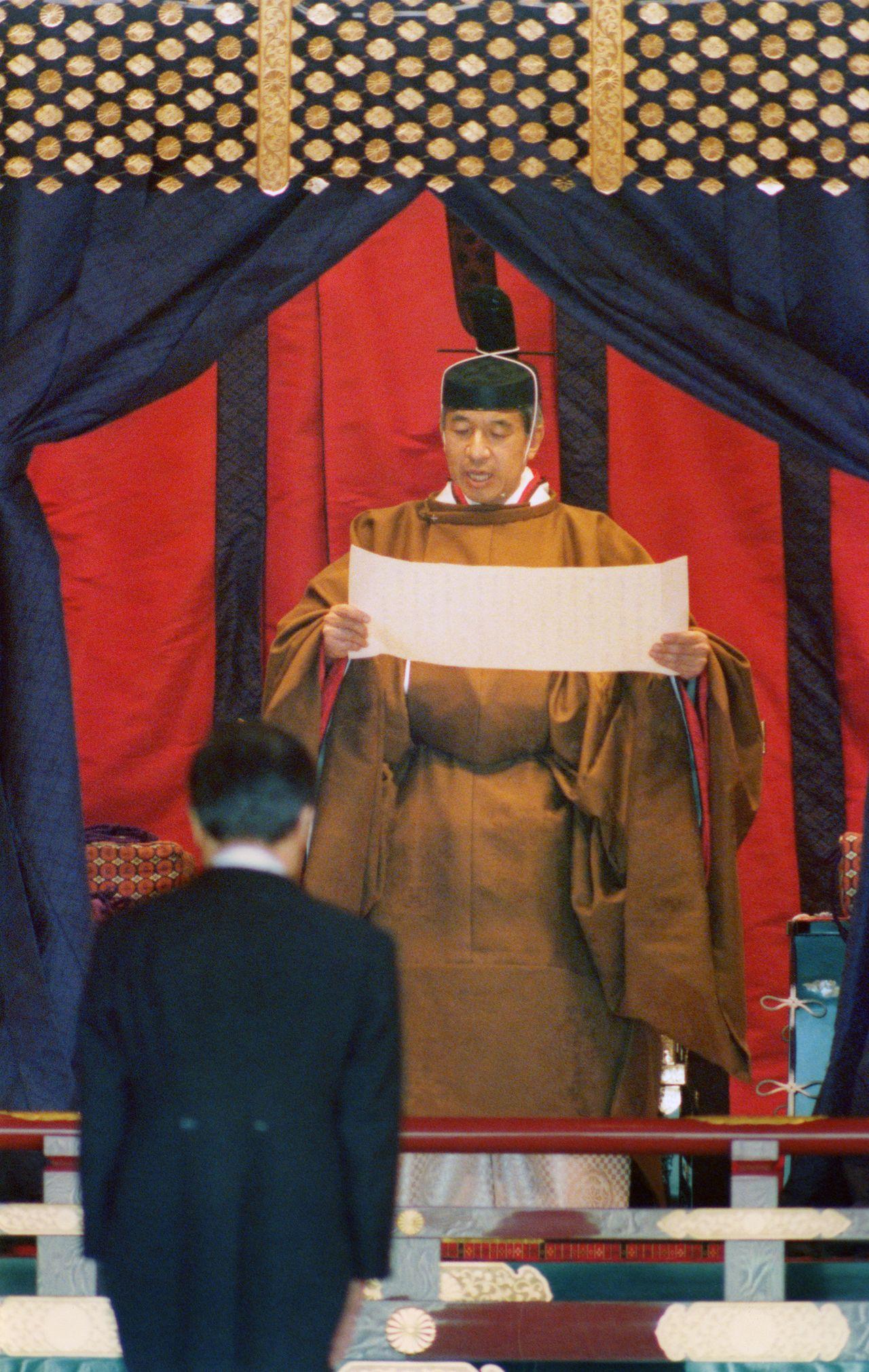 Император Акихито (нынешний почётный император) читает речь во время церемонии Сокуирэй Сэйдэн-но ги. 12 ноября 1990 г., зал Мацу-но ма (Jiji Press)