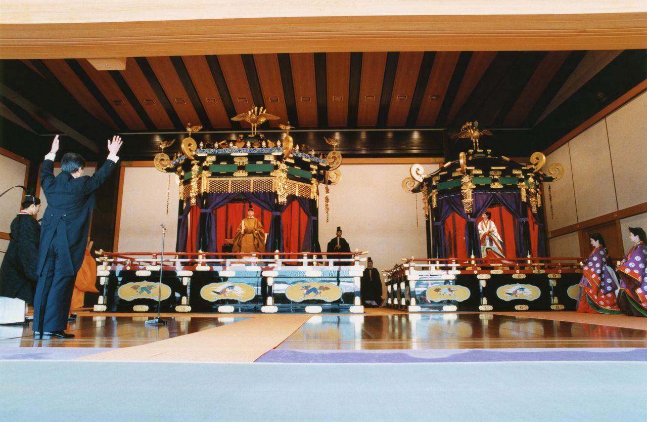Император и императрица (нынешние почётные император и императрица) во время церемонии Сокуирэй Сэйдэн-но ги; слева премьер-министр Кайфу Тосики трижды возглашает «Бандзай!». 12 ноября 1990 г., зал Мацу-но ма (Jiji Press)