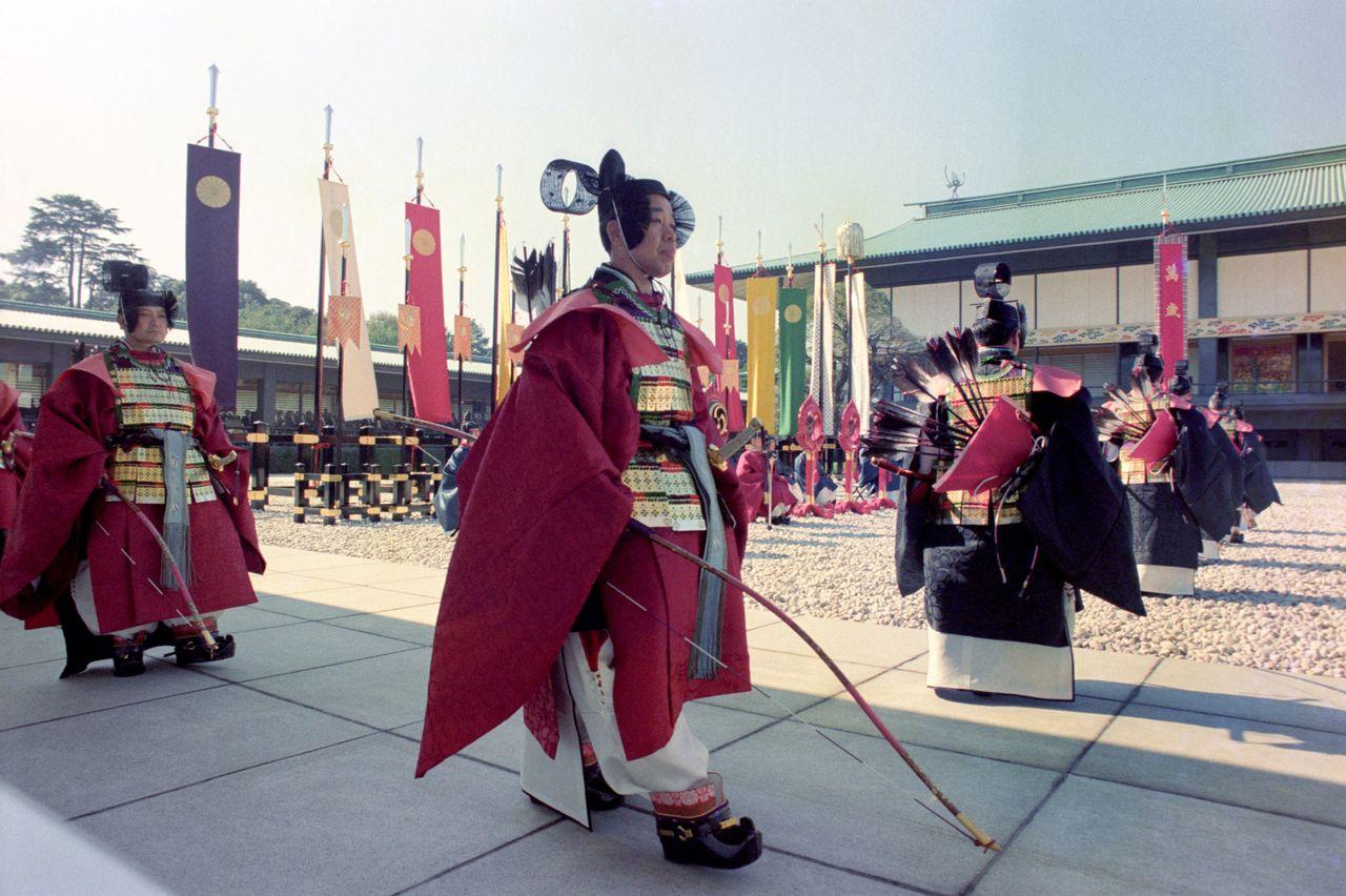 Украшения, знаки императорского достоинства и работники Управления императорского двора в старинных одеждах во внутреннем дворе дворца перед залом Мацу-но ма во время церемонии Сокуирэй Сэйдэн-но ги. Ноябрь 1990 г., («Ёмиури симбун»/Aflo)