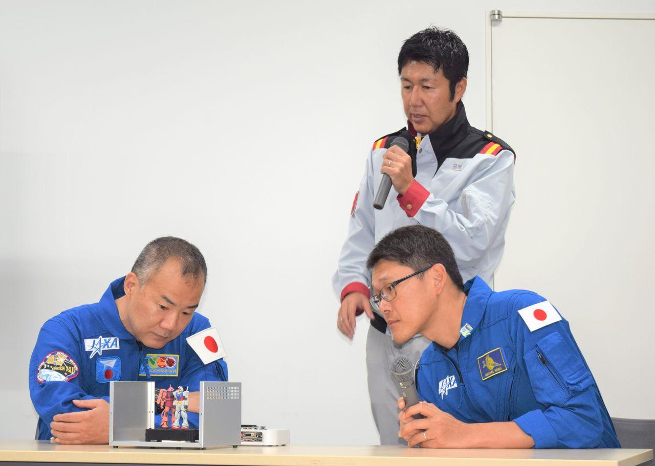Участники проекта «G-SATELLITE – в космос» осматривают фигурки Гандама, устанавливаетсяе в спутник (4.09.2019, г. Сидзуока, р-н Тиёда Аои, фото Jiji Press)