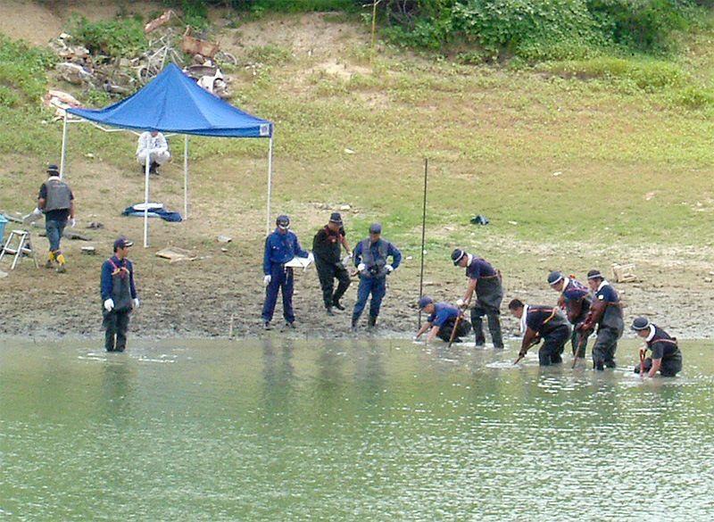 12 августа 2005 года полиция префектуры Осака обыскивает пруд в поисках вещей жертвы серийного убийцы (© Jiji)