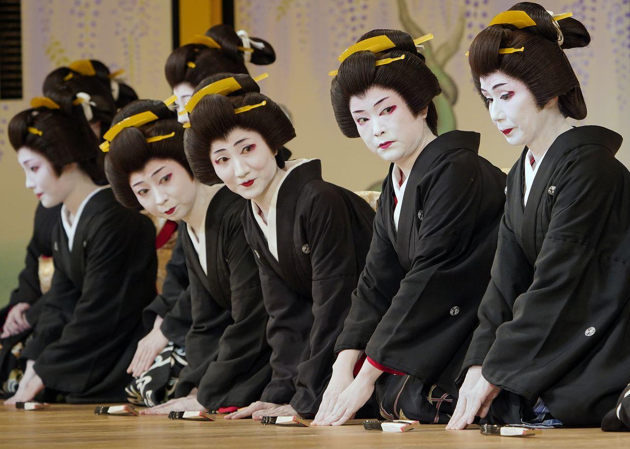 Форменная одежда гейш – чёрное кимоно косодэ с короткими рукавами и гербами, белый воротник, причёска симада-магэ. Репетиция накануне представления в театре «Симбаси эмбудзё», созданного для демонстраций достижений гейш в искусстве (май 2019 г., Jiji Press)