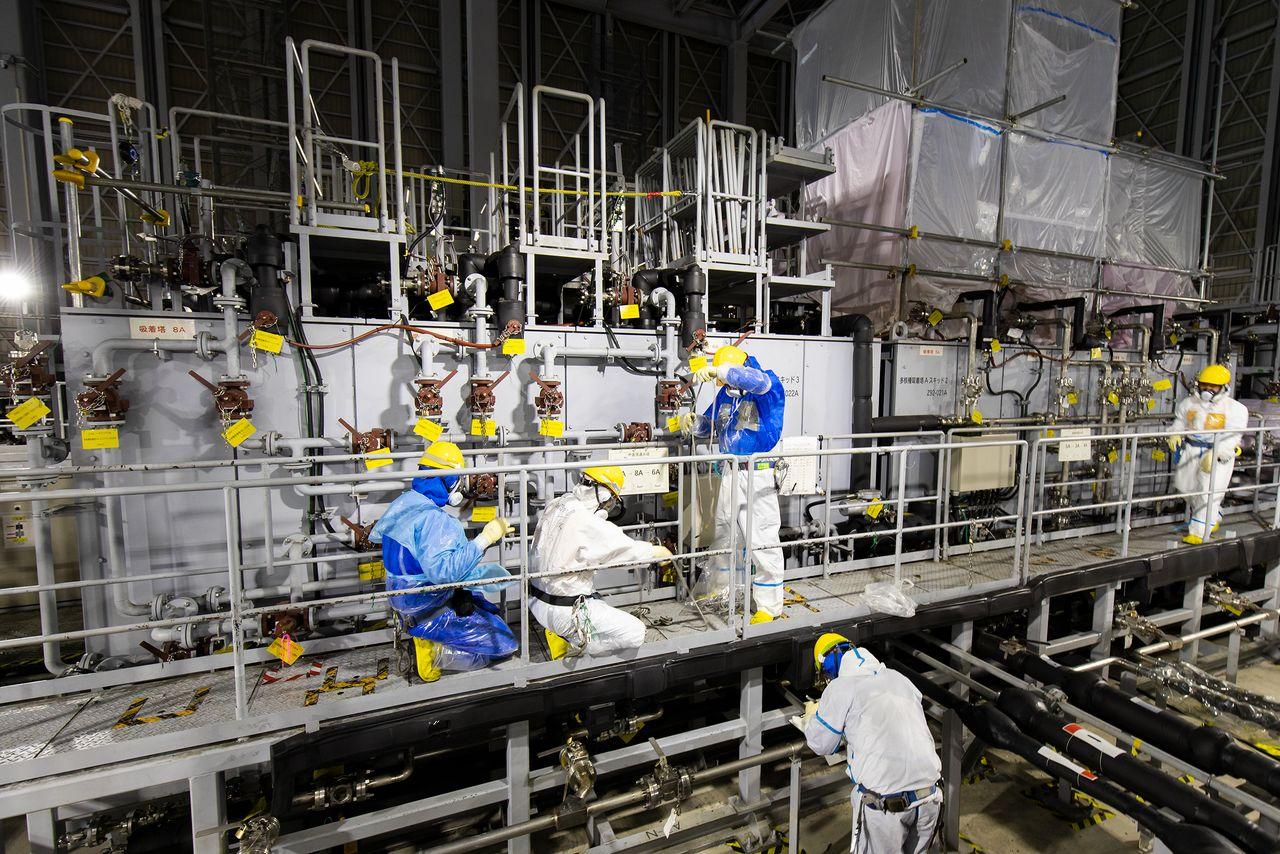 В помещении системы ALPS, способной извлекать из воды 62 вида радиоактивных веществ. Рабочие деловито снуют в полной экипировке: защитных костюмах, защитных масках на все лицо и двуслойных перчатках