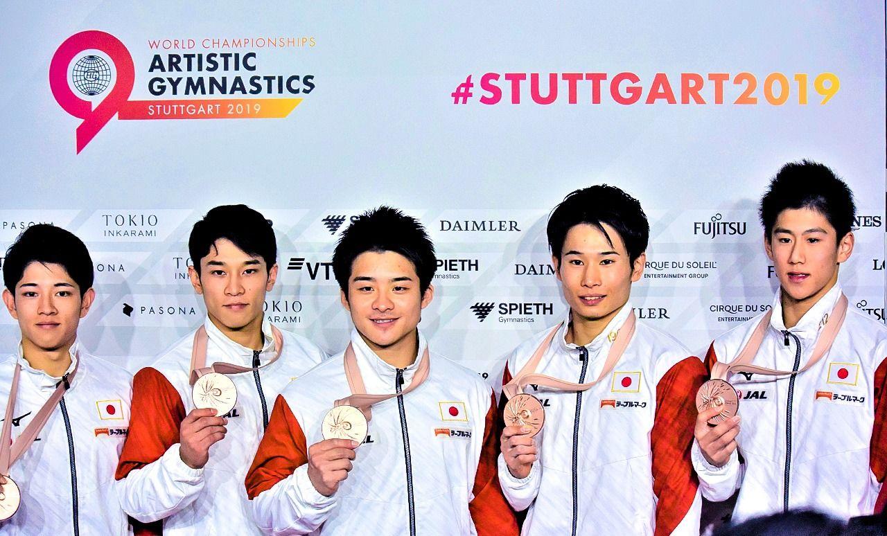 Хасимото Дайки (справа) демонстрирует бронзовую медаль вместе с членами японской сборной по гимнастике на Чемпионате мира в Штутгарте (@Янаи Юкико)