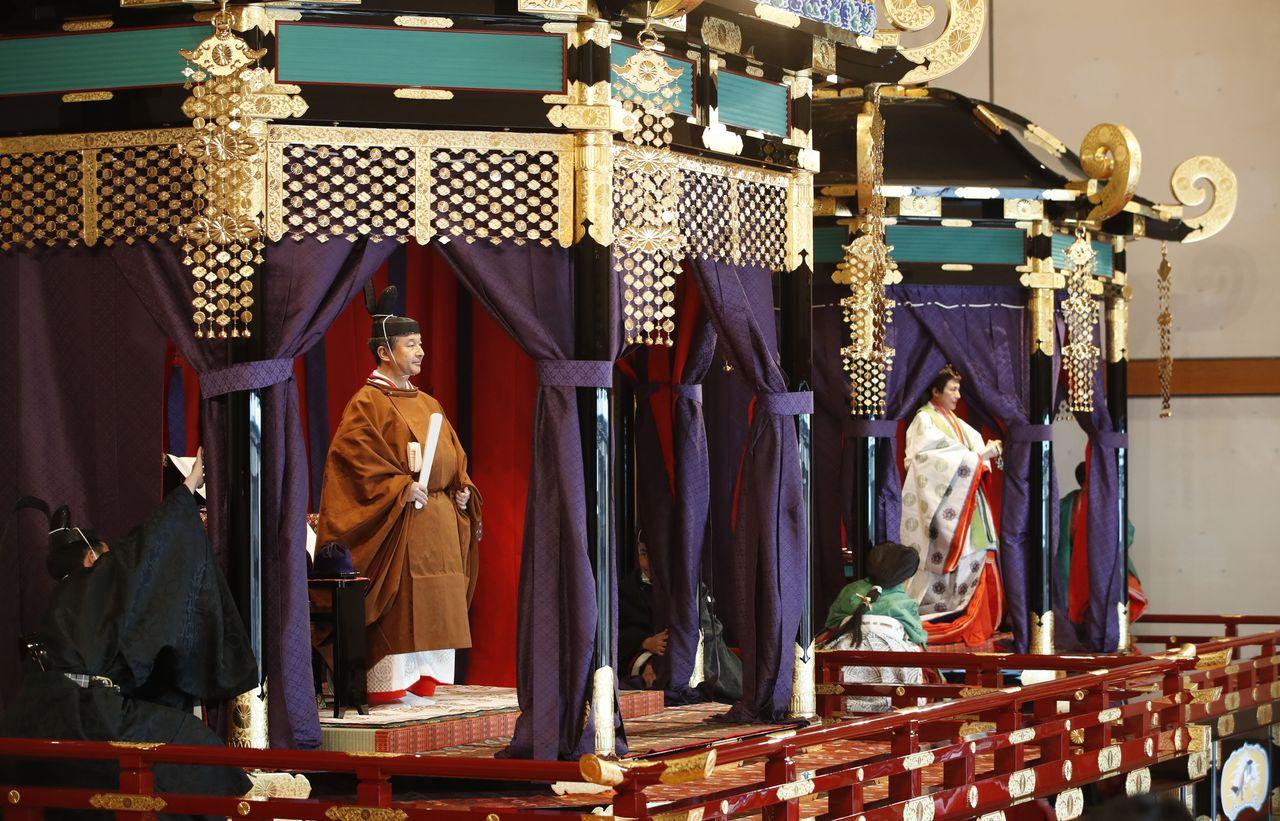 Император Нарухито стоит на троне Такамикура, представляющем собой 8-тонную платформу с крышей и восьмиугольным постаментом. Императрица Масако стоит на Митёдай, немного меньшей по размеру церемониальной платформе (© Jiji)