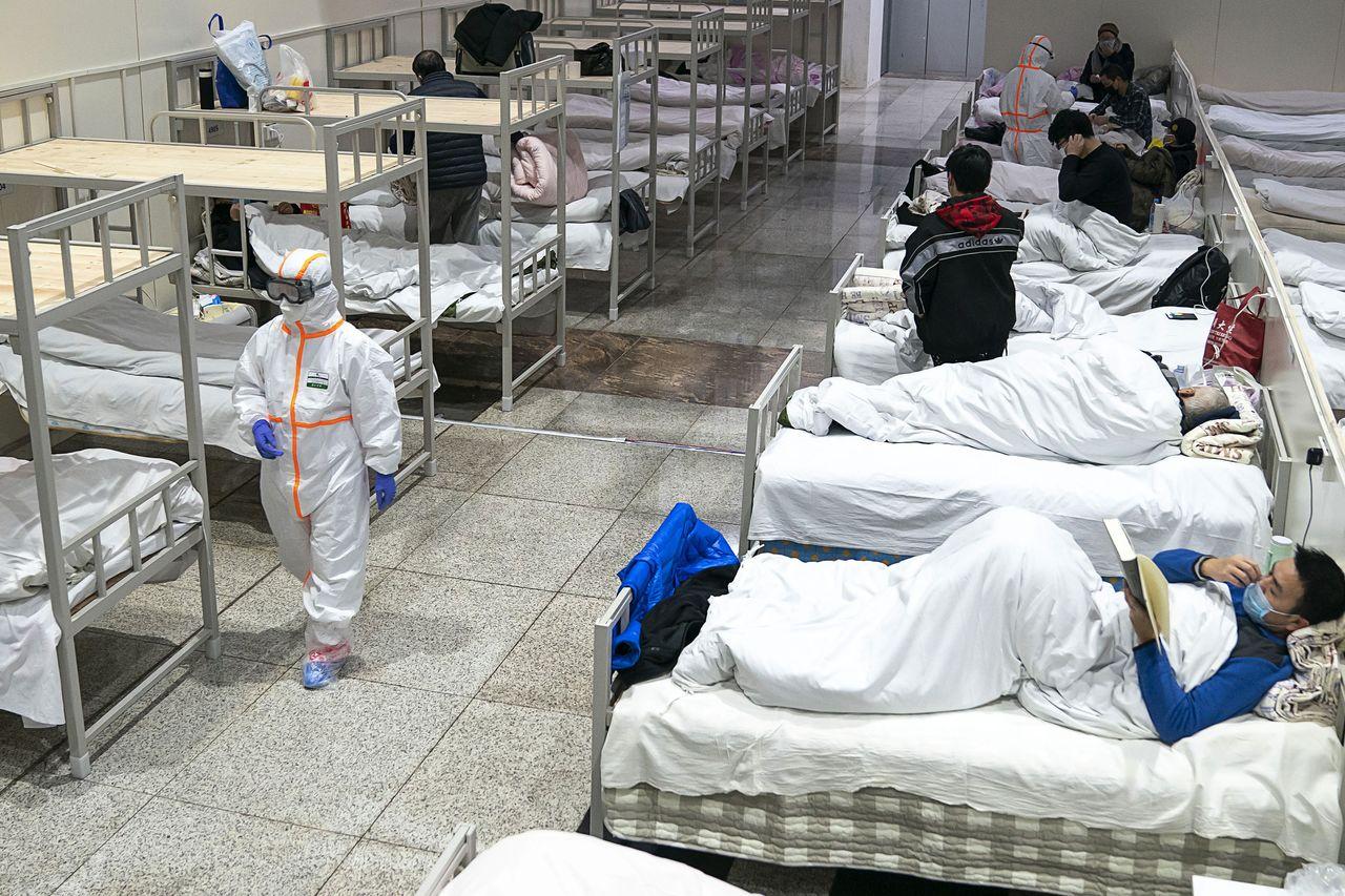 Медицинский работник в защитном костюме проходит мимо пациентов с коронавирусом, которые проходят лечение во временной больнице, расположенной в выставочном центре в Ухане, провинция Хубэй, 5 февраля 2020 г. (© Chinatopix / AP / Aflo)