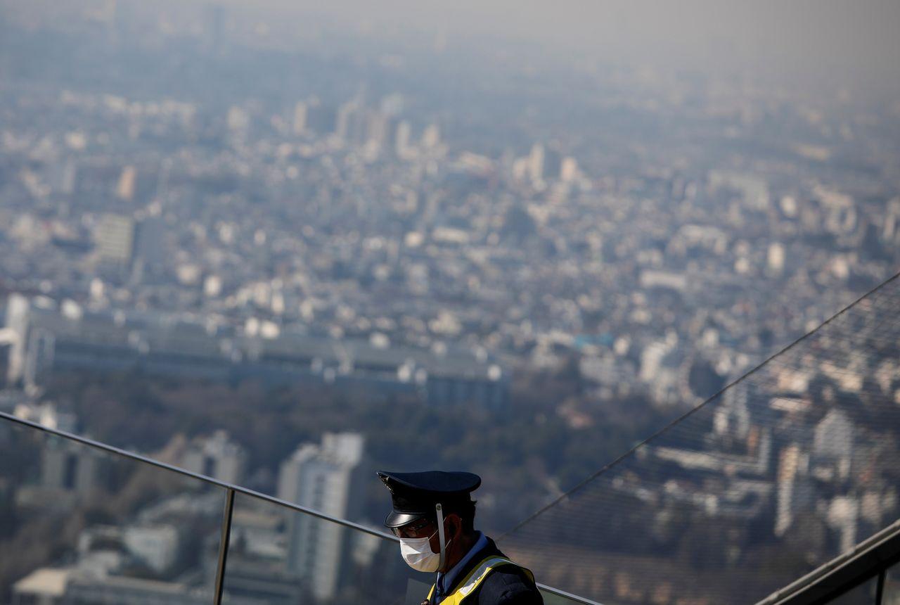 ФОТОГРАФИЯ: Охранник в защитной маске во время вспышки коронавирусной болезни (COVID-19) на смотровой площадке в Токио, Япония, 22 января 2021 года. REUTERS / Issei Kato