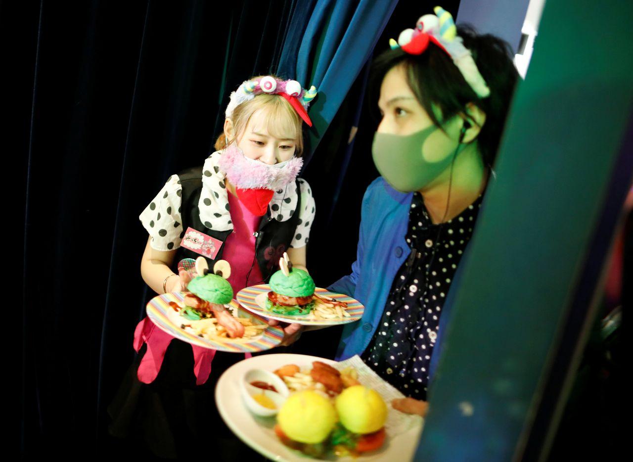 Сотрудники в защитных масках подают еду гостям в Kawaii Monster Cafe во время вспышки коронавирусной болезни (COVID-19), Токио, Япония, 31 января 2021 г. REUTERS / Issei Kato