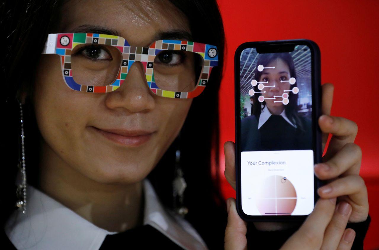 Сотрудник интернет-магазина модной одежды Zozo Inc позирует с очками Zozoglass и приложением для смартфона, используемым для измерения тона кожи при заказе косметики в Интернете, во время демонстрации в офисе компании в Токио, Япония, 28 января 2021 г. Снимок сделан 28 января 2021 г. REUTERS / Kim Kyung-Hoon