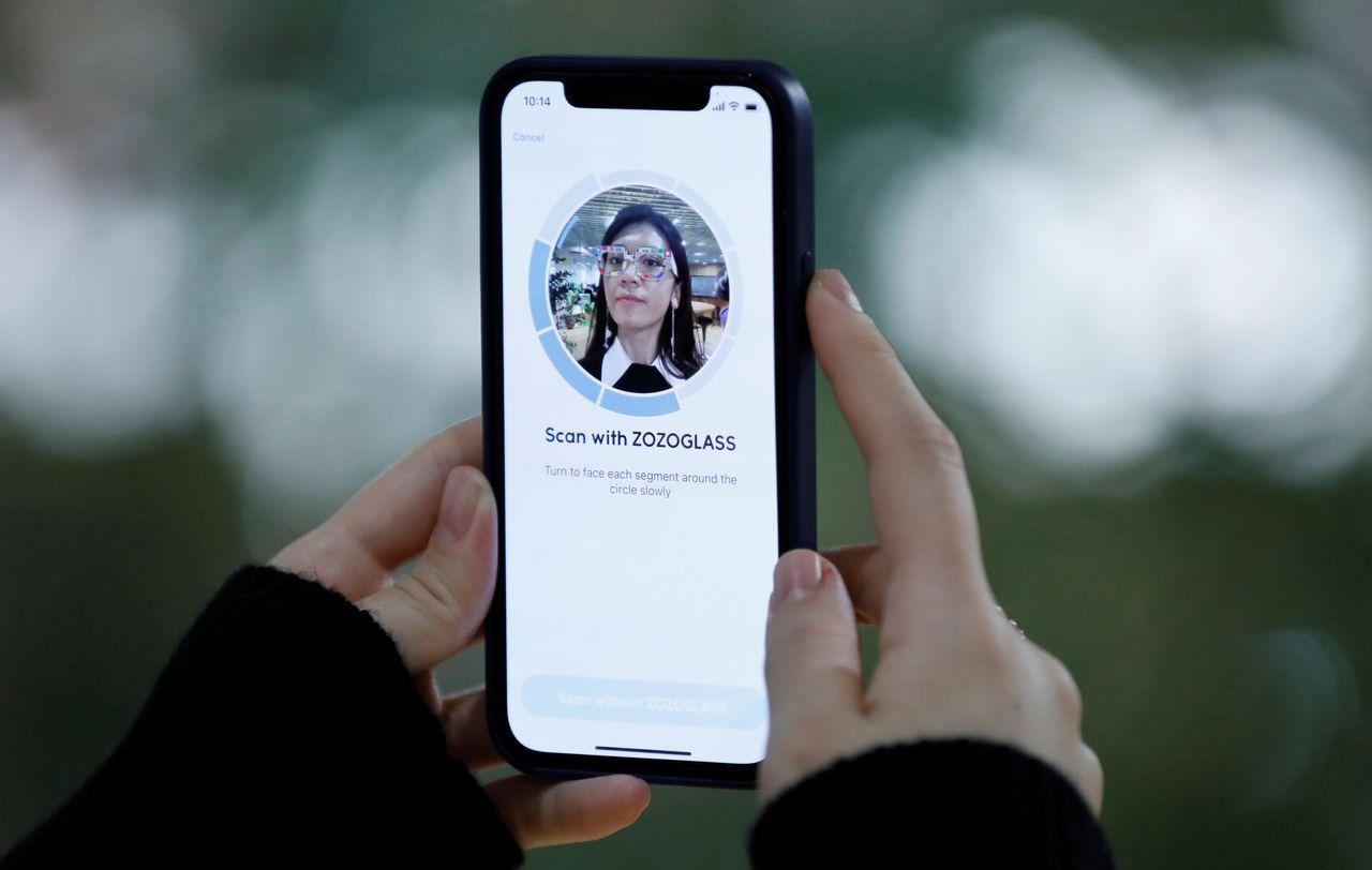 Сотрудник интернет-магазина модной одежды Zozo Inc демонстрирует приложение для смартфона Zozoglass, используемое для измерения тона кожи для онлайн-заказа косметики, в офисе компании в Токио, Япония, 28 января 2021 г. Снимок сделан 28 января 2021 года. REUTERS / Kim Kyung -Hoon