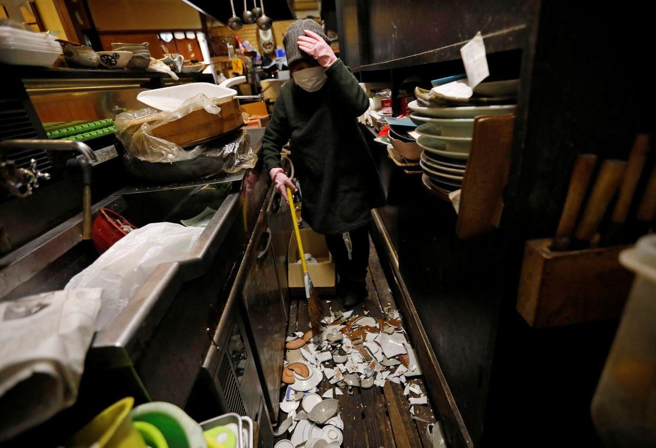 70-летняя Мицуэ Хиса, владелица японского паба идзакая, убирает разбитую посуду в своем заведении после сильного землетрясения, город Иваки, префектура Фукусима, Япония, 14 февраля 2021 года. REUTERS / Issei Kato