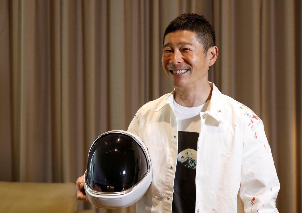 Японский миллиардер Маэдзава Юсаку позирует со шлемом скафандра во время интервью Reuters в Токио, Япония, 3 марта 2021 г. REUTERS / Kim Kyung-Hoon