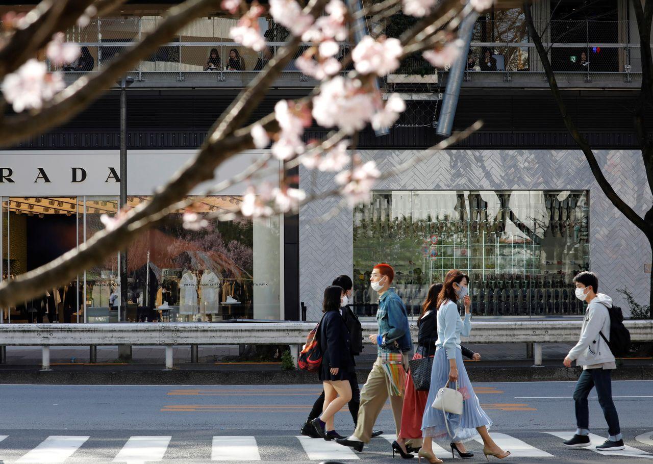 ФОТОГРАФИЯ: Пешеходы в защитных масках во время вспышки коронавирусной болезни COVID-19 любуются цветами сакуры в Токио, Япония, 18 марта 2021 г. REUTERS / Kim Kyung-Hoon