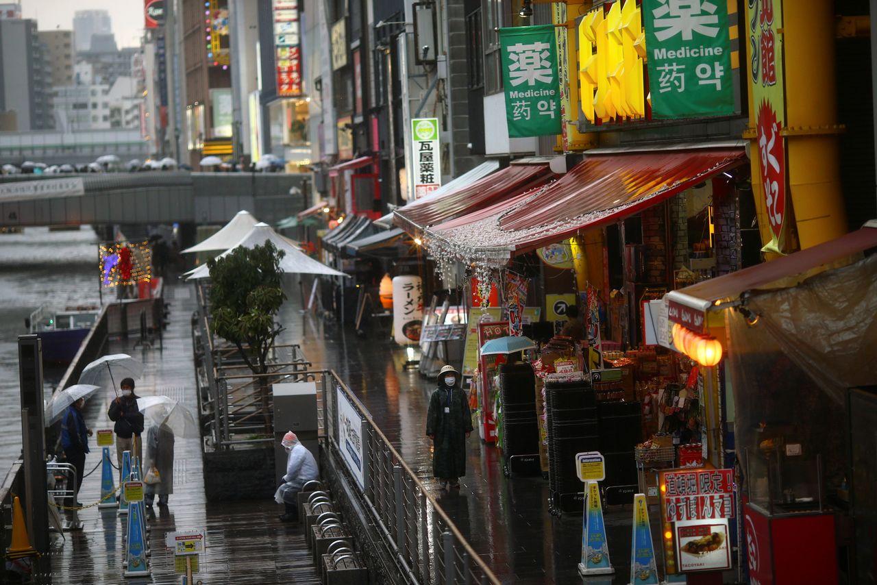 ФОТОГРАФИЯ: Женщина в защитной маске после вспышки коронавирусной болезни (COVID-19) идёт по почти пустой улице развлекательного района Дотомбори в Осаке, Япония, 14 марта 2020 г. REUTERS / Edgard Garrido
