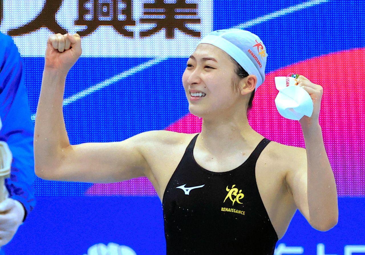 Икээ Рикако позирует перед болельщиками, одержав победу в женском заплыве на 100 метров баттерфляем, 4 апреля 2021 г., Tokyo Aquatics Centre (официальная съемка)